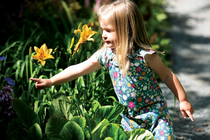 A little girl wearing Frugi's Esther Playsuit in a ditsy floral print points to the purple and yellow flowers around her.